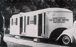 Photo of a 1937 trailer hitiched to the back of a car. The trailer is marked with the words Electrification Electric Home equipment.