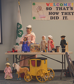 Young girl in pink dress with four dolls on a table and one doll in the floor with a horse and buggy.