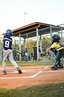 Young boy in blue helmet and jersy swinging a bat to hit a ball at a baseball game.