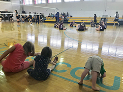Three kids stretchering in gym while vollyball players in background are also stretching.