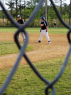 Photo taken through fence of two young boys on opposite teams playing baseball.